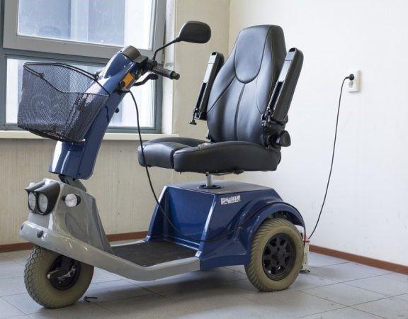 Elektrische driewielige scootmobiel staat op te laden in een stopcontact.
