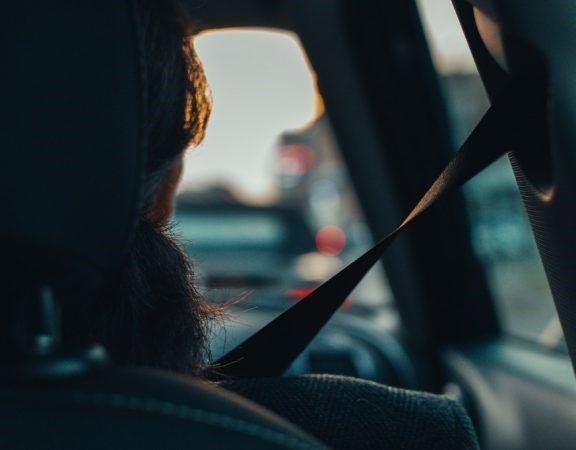 Inzittende vanaf de achterbank gefotografeerd, draagt een autogordel.