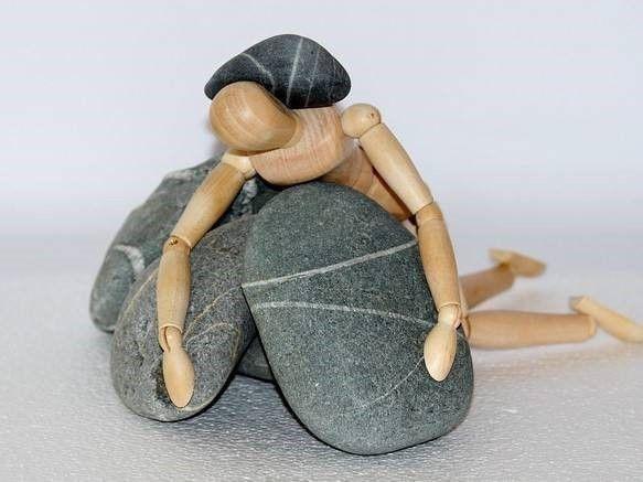 Houten figuur met steen: Bedrijfsongeval: cliënt krijgt zware deur tegen zijn hoofd