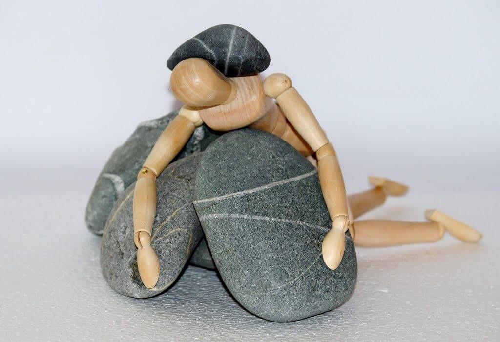 Geveld door whiplash: houten poppetje ligt met zijn gezicht naar de grond gericht op een paar stenen. Een steen ligt op zijn nek.