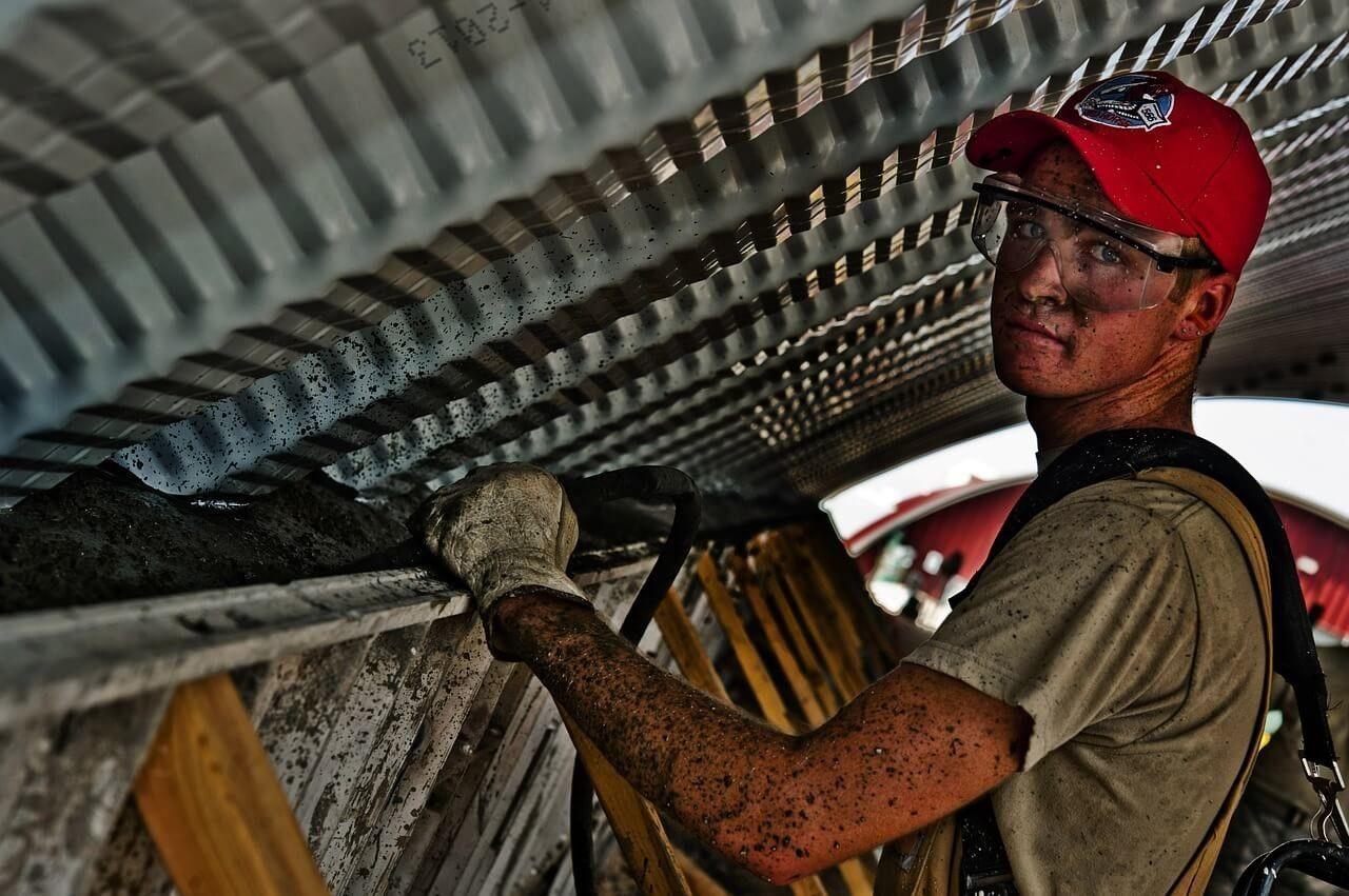 Man aan het werk in de bouw met veiligheidsbril op en handschoenen aan