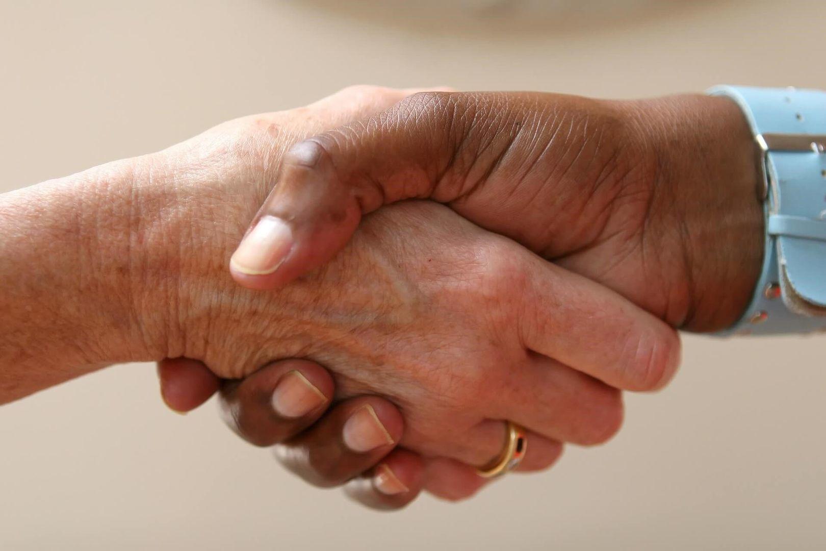 De juiste advocaat of andere letselschadespecialist zal u de hand schudden, zoals deze twee mensen op de foto doen.